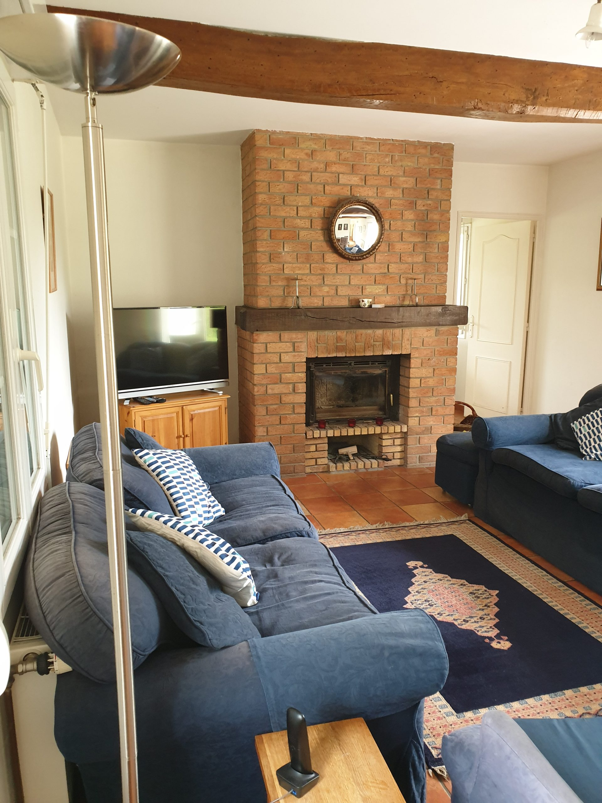 Living Room with wood burning stove and doors leading onto both front and rear patio areas and garden